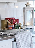 Dish of storage tins, tea towel and vintage-style, white-painted lantern on kitchen counter