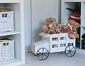 White-painted, rustic, wooden toy truck loaded with soft toys