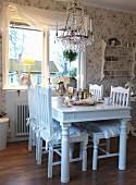 Essplatz am Fenster mit weiss lackiertem Holztisch und Stühlen, in ländlichem Stil, oberhalb Kronleuchter mit Glasschmuck