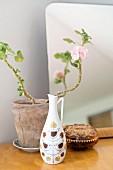 Still-life arrangement in retro jug-style vase, delicate geranium in clay pot and jewellery box