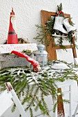 Festive arrangement with Welcome sign outside house with figurines, lanterns, ice skates and fir branches