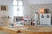 Romantic, white, shabby-chic sitting area on curved wooden dais; festive wreaths hung from red ribbons