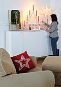 Festive arrangement on sideboard with woman lighting candles behind cushion with star motif on armchair