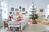 Festively decorated dining table and Christmas tree in interior of Scandinavian wooden house