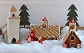 Wooden model of Swedish church, gingerbread houses and Father Christmas figurines in artificial snow
