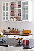 Red and white beakers on breakfast bar and plate rack integrated into wall cabinet