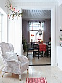 View from foyer with white rattan chair to traditional dining area with festive decorations