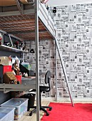 Teenager's metal loft bed with integrated desk; wall decorated with front pages of English newspapers