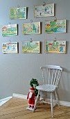Colourful children's drawings above traditional wooden chair next to Father Christmas figurine at head of staircase