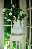 White china jug of jasmine on flower stand