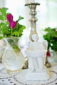 White china angel figurine next to glass vase of purple flowers