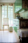 White chair in front of floor-to-ceiling lattice window and fitted cupboards with green doors in rustic kitchen