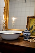 Vintage metal wash basin and chine pot with lid in front of gilt-framed mirror