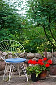 White, delicate metal chair with blue seat cushion next to red geraniums on stone floor in front of low garden wall with view into garden
