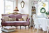 Baroque-style sofa with lilac velvet cover, scatter cushions and white dining set