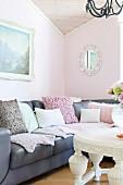 Graue Ledercouch mit verschiedenen Kissen und weisser Couchtisch im Wohnzimmer mit pastellrosa getönter Wand