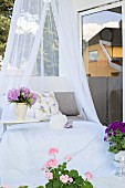 Daybed with canopy and flowers in shades of purple on terrace
