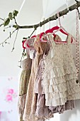 Branch used as clothes rack holding vintage-style girl's clothing