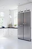 Schwarz-weisse, skandinavische Landhausküche mit doppeltürigem Edelstahlkühlschrank
