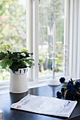 Scandinavian ceramic pot of hydrangeas and candlestick on black surface in front of window