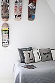 Kissen mit Typo-Print auf Jugendbett mit Tagesdecke; Wanddeko mit abgewetzten Skateboards