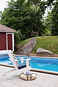 White chair on wooden deck next to pool with garden view