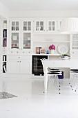 Weisser Esstisch mit Klassikerstühlen von Eames vor weisser Anrichte in ländlichem Esszimmer