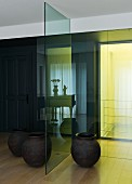 Simple floor vases either side of glass partition, yellow light streaming into foyer