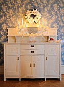 Crystal candelabra with lit candles on white-painted cabinet with top section against wallpaper with white floral pattern on blue background