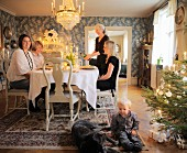 Toddler and dog sitting on rug next to Christmas tree in front of family around dinner table in traditional dining room