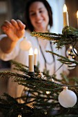 Woman decorating Christmas tree - candle-shaped fairy lights and baubles on branches