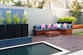 Sunken pool on modern patio, bench with seat cushions and euphorbia in black planters in front of high concrete wall
