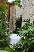 Free-standing bathtub with floor-mounted taps in idyllic garden in front of high stone wall with outdoor shower