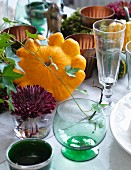 Autumnal arrangement of pattypan squash, ivy, moss and drinking glasses on table