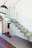 Concrete staircase with floating steps and glass balustrade in foyer