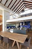Heller Holz Esstisch und gepolsterte Stühle mit grauem Stoffbezug vor Kochinsel, darüber Galerie und Blick in Dachstuhl eines offenen Landhauses