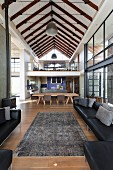 View from lounge area with black leather sofa set and vintage rug to dining area and mezzanine below exposed roof structure in contemporary home