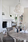 Dining area with grey, upholstered chairs around wooden table below pendant lamp with capiz shell lampshade in rustic interior