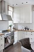weiße Landhausküche mit Edelstahlherd, im Vordergrund grauer Polsterstuhl
