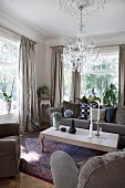 Wooden coffee table and grey sofa set in living room with Venetian-style glass chandelier hanging from stucco ceiling rose