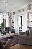 Polstersessel mit grauem Samtbezug und Couchtisch in elegantem Wohnzimmer, im Hintergrund massgefertigtes Bücherregal in Weiss mit integrierten Schiebetüren