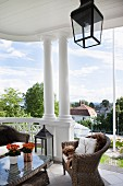 Wicker armchairs and table on roofed, old-fashioned terrace with columns