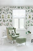 Reading chair with matching footstool below window; white wainscoting below decorative wallpaper with pattern of fern