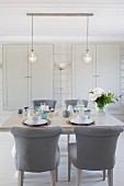 Chairs with grey upholstery at set table below two pendant lamps