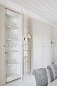 Blick über gepolsterte Stühle, auf Vitrinen Einbauschrank, an Wand und Decke weisse Holzverkleidung