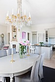 Chairs with grey loose covers around neo-classical dining table below chandelier in open-plan interior with kitchen area