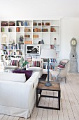 Table lamp on wooden side table and armchairs in front of fitted bookshelves