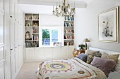 Double bed with patterned bedspread and many scatter cushions in rustic bedroom with custom wardrobes and white shelving