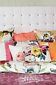 Floral and plain scatter cushions against white button-tufted headboard
