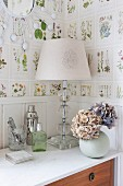 Tischleuchte mit weißem Schirm und Hortensien in Kugelvase auf Kommode, an Wand Tapete mit botanischem Muster